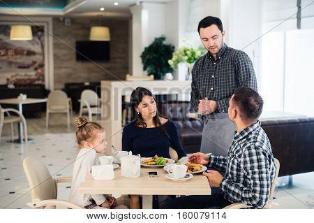 Happy family having breakfast at a restaurant.
