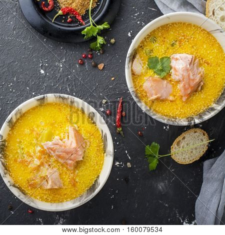 Intense fragrant homemade thick rich soup with salmon in a la carte dishes against a dark background. Top view