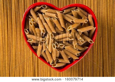 Wholemeal Pasta. Integral Penne Into A Heart Bowl Over A Wooden Table Top View