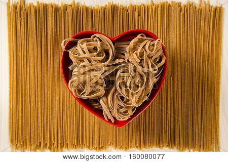 Wholemeal Pasta. Integral Tagliatelle Into A Heart Bowl Over A Wooden Table Top View