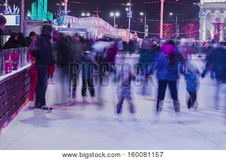 Blurred photo. Funny kids, families together in evening time outdoors in the park on winter skating rink. Christmas, sport and healthy lifestyle, fun in wintertime.