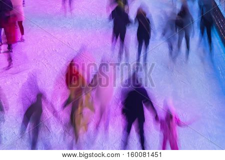 Blurred image of ice rink with people in evening time outdoors in the park on winter. Sport and leisure concept - skating on rink outdoors, fun, wintertime. With place for your text, for background use.