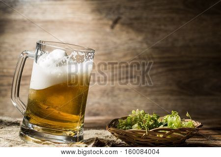 Frothy beer spills from tankard on empty wooden background next to hop in basket