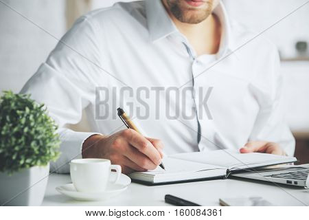 Close up of businessman at office desktop writing in organizer. Business concept