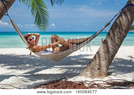 Woman lying in a hammock in the shade of palm trees