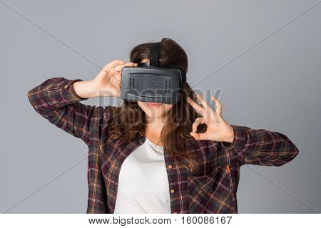 young charming girl in virtual reality helmet in studio on grey background