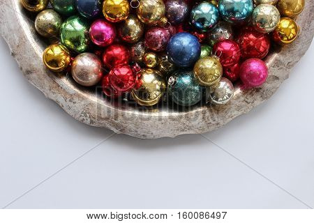 Silver platter filled with piled high colorful, vintage ornaments. Open space for copy.