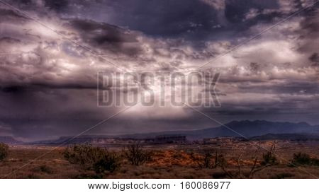Storm clouds open up over a desert landscape.