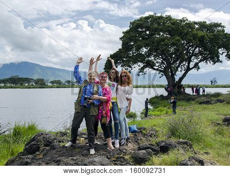 AFRICA, TANZANIA, MAY, 10, 2016 - Funny girls travellers on Africa posing for photos on a background the lake Manyara on the memory together in Ngorongoro Crater, national park Tanzania.