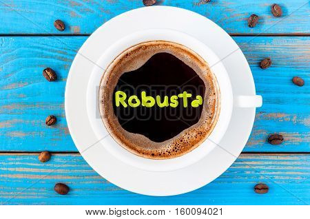 Robusta - sort of coffee, written on morning coffees mug at blue wooden table with beans.