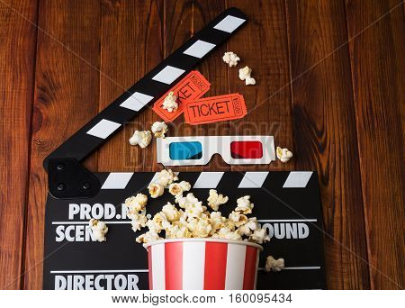 Movie clapper, popcorn, 3d glasses on a wooden background