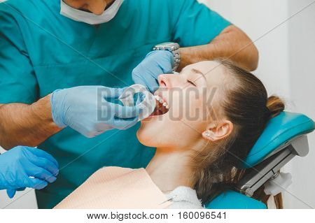 Doctor dentist puts the retractor to the patient.