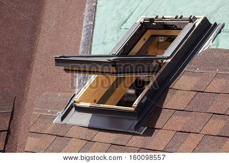 Open skylight on a roof shingles under construction