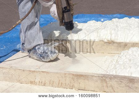 Technician spraying foam insulation using Plural Component Spray Gun