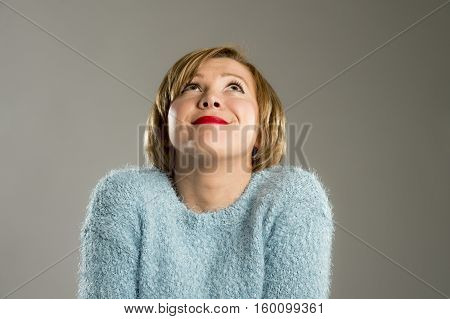 candid portrait of young beautiful and sweet woman in blue pullover smiling happy and cheerful in friendly face expression isolated on grey background in happiness concept