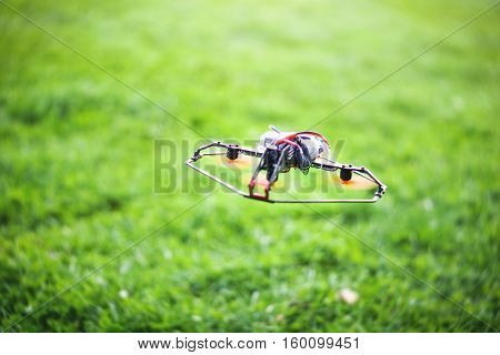 Flying smart drone on a background of green grass - Innovation and technology concept