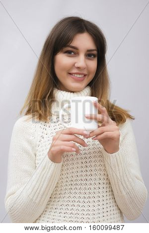 Portrait of young brunette woman in sweater drinking coffee or tea on light grey background
