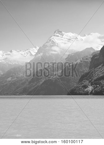 Grandiose mountain landscape. Mountain tops in the snow. White sail on a romantic lake. Black and white