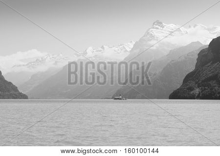 Grandiose mountain landscape. Mountain tops in the snow. Steamship floats on the lake. Black and white