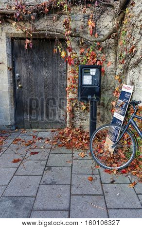 Broad Street Oxford United Kingdom December 04 2016: Oxford parking meter with Out of order notice sticker with bicycle and add board on Broad Street Oxford.
