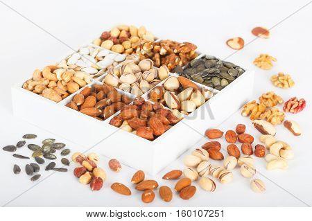 Mix of nuts in wooden box: walnut, Brazil nut, pistachios, almond, peanut, cashew, hazelnut and pumpkin seed
