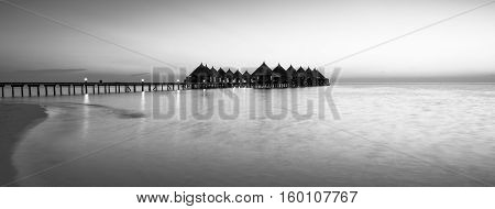 Panorama of tropical island resort with overwater bungalows at night in black and white. Maldives. Ari Atoll.