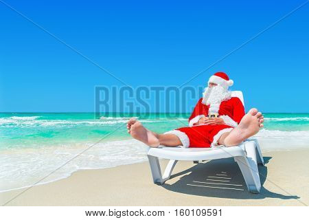Santa Claus relax on sunlounger at ocean tropical sandy beach. Meкry Christmas and Happy New Year travel destinations concept.