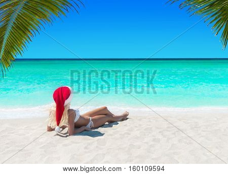 Cute blonde Snow Maiden woman in Santa hat take pleasure sunbathing at tropical ocean palm beach Christmas and New Year travel destinations to vacation in hot countries concept