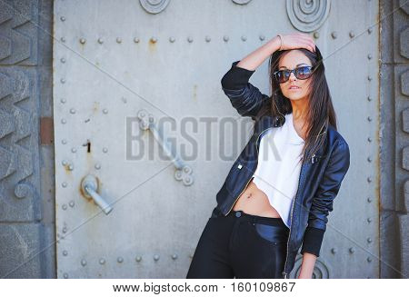Young slim beautiful brunette girl wearing sunglasses in a short white tank top leather jacket and jeans straightens her long hair with a hand in the background of the iron doors.