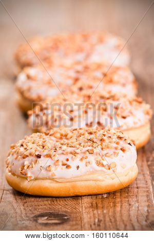Sweet donuts with sprinkles on wooden table.