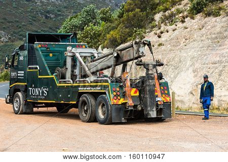 Toitskloof pass, South Africa - November 21, 2016: The driver of a heavy duty wrecker used for towing semi trucks is making a break before towing a large truck along the garden route near Cape Town in South Africa.
