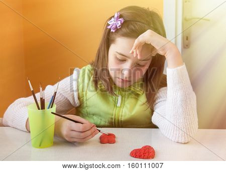 a young girl painting handmade gift in the form of Heart