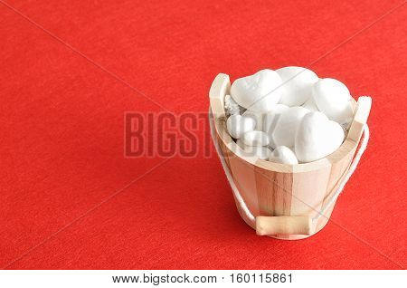 Valentines day. A wooden bucket filled with polystyrene hearts isolated against a red background
