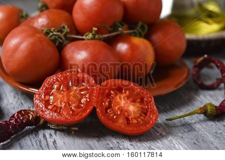 closeup of a pile of tomates de colgar, a typical spanish species of tomatoes, in an earthenware plate, on a rustic wooden table and a cruet with olive oil in the background