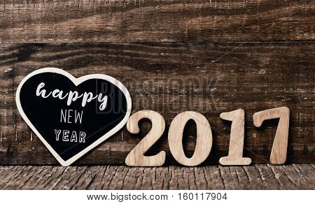 heart-shaped black signboard with the text happy new year written in it and some wooden numbers forming the number 2017 placed on a rustic wooden surface