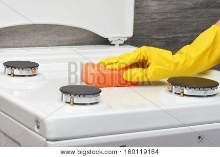 Hand In Yellow Glove Cleaning White Stove With Orange Sponge