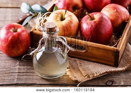 Bottle of unfiltered apple cider vinegar and apples in a wooden box over rustic background close up