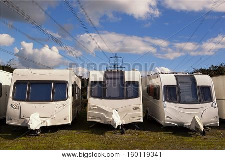 Three Caravans stored in rows on a sunny day with clouds in the sky with electricity cables in the background. Space for text.