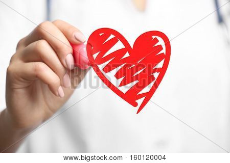 Cardiologist drawing heart, closeup. Cardiology concept.