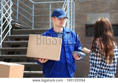 Woman paying for delivery with credit card and payment terminal
