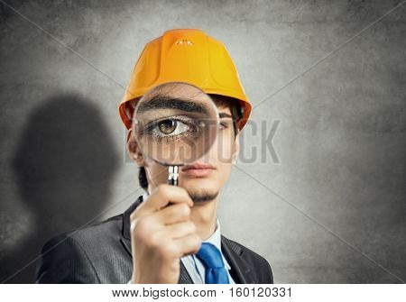 Portrait of engineer man in helmet looking through magnifying glass