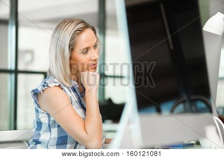 Attractive woman sitting at desk in modern office