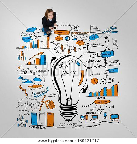 Top view of businesswoman and business strategy sketches on floor