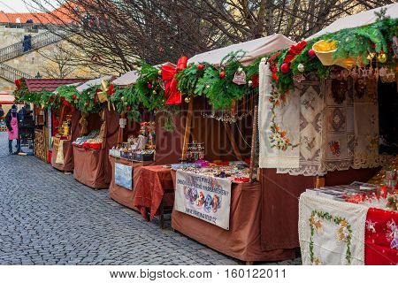PRAGUE, CZECH REPUBLIC - DECEMBER 10, 2015: Wooden decorated stalls with traditional products at Christmas market in Old Town of Prague - famous annual winter fair taking place in december.