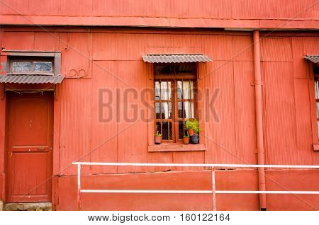 A bright clear red brightens the corrugated siding of this house in Valparaiso Chile.