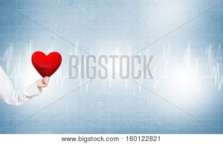 Hand of woman doctor against blue background holding red heart