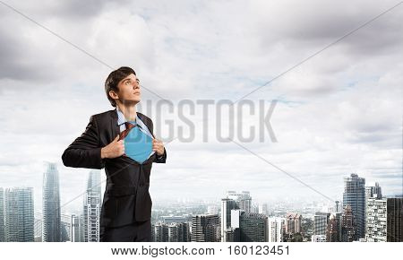 Office worker opening his shirt like superhero on modern city background