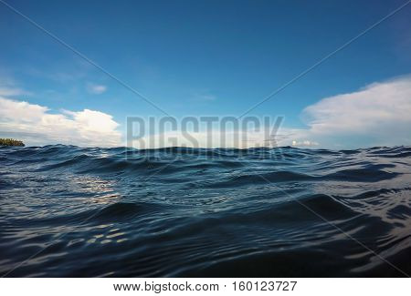 Double landscape water and sky photo. Sea and sky double background. Seaside image. Above and below waterline. White fluffy clouds card. Ocean ripple. Seawater closeup. Banner template with text space