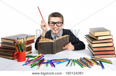 Cute Boy Reading A Book With Glasses. Happy Child Sitting With A Book At The Table.