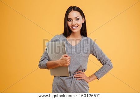 Model holding laptop in hand. one hand at hip. isolated orange background